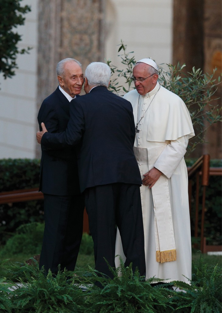 Pope Francis looks on as Israeli President Shimon Peres, left, and Palestinian President Mahmoud Abbas embrace during an invocation for peace in the Vatican Gardens, June 8.