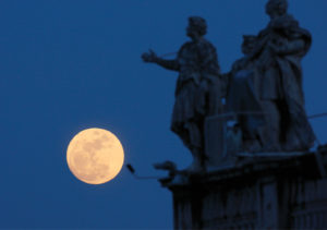 CNS photo/Paul Haring A full moon is juxtaposed with statues of saints on the colonnade in St. Peter's Square.
