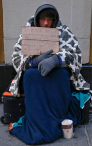 "A man holding up a sign stating he is 'homeless, hungry and cold' sits along the sidewalk in New York Jan. 8. Under an umbrella organization called Circle of Protection, more than 100 Christian faith leaders want any and all presidential candidates, but especially ""major"" candidates, to make poverty a priority throughout the 2016 election campaign. (CNS photo/Shannon Stapleton, Reuters)"